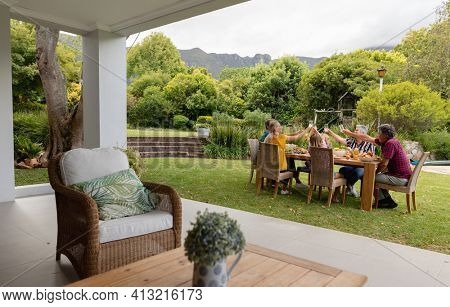 Caucasian three generation family sitting at table making a toast during meal in garden. three generation family celebrating eating outdoors together.