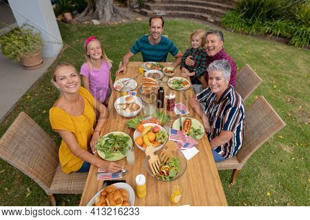 High angle view of smiling caucasian three generation family having celebration meal in garden. three generation family celebrating independence day eating outdoors together.