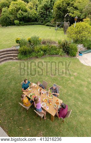 High angle view of caucasian three generation family sitting at table eating meal in garden. three generation family celebrating eating outdoors together.