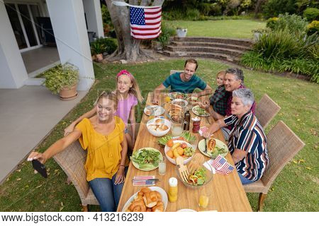 Caucasian woman taking selfie with three generation family having celebration meal in garden. three generation family celebrating independence day eating outdoors together.