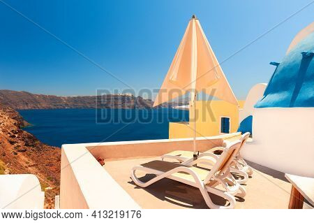 Santorini Island, Greece. Two Chaise Lounges On The Terrace With Sea View. Travel Destinations Conce