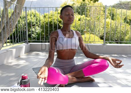 African american woman practicing yoga sitting meditating on sunny garden terrace. staying at home in isolation during quarantine lockdown.