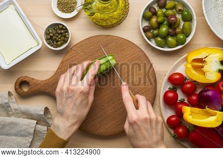 Vegetarian Food. Chopping Cucumber, Cutting Vegetables For Greek Salad Horiatiki. Woman Hands With K