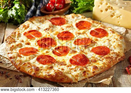Pepperoni or Salami Pizza - homemade pizza dough topped with salami sausage slice and cheese. Italian pizza on baking paper with tomato and cheese on wooden table. Fast food dinner in rustic style