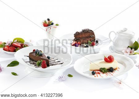 Dessert Table - created with Chocolate Cake, Classic Cheesecake, Ice Cream  and Chocolate Cheesecake. Fresh spring flowers on white table with berries and tea pot. Cake topped with berries and chocola