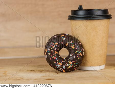 A chocolate frosted donut or doughnut leaning on a hot cup of fresh brewed coffee. coffee and donut for breakfast