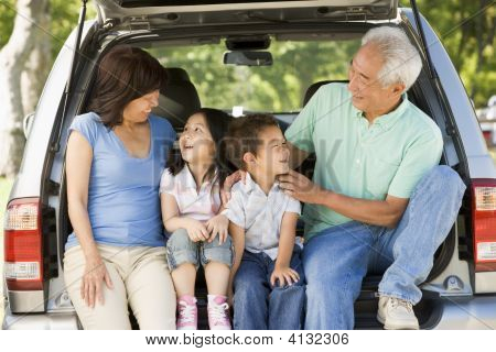 Grandparents and grandchildren sitting in the boot of a car poster