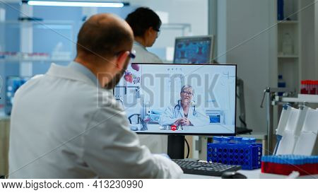 Senior Woman Doctor Offering Medical Online Advices To Chemist Using Pc Webcam. Scientist Holding Bl
