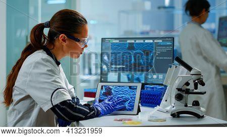 Scientist Using Digital Tablet Analysing Virus Evolution, Treatment Development In Medical Research