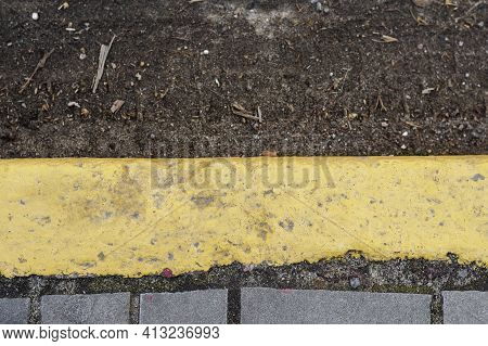 The Yellow Curb At The Edge Of The Dirt Road. The Marking Of The Bus Stop. View From Above. Selectiv