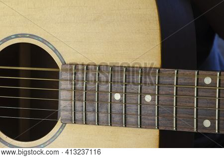A Trembling String On An Acoustic Guitar, Motion Blur. Vibration Of The Sixth String Of A Yellow Gui