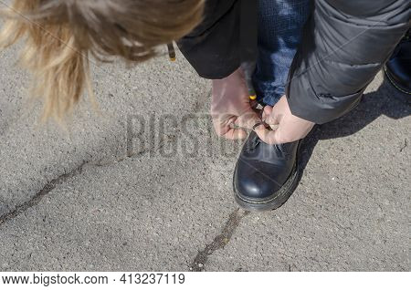 A Woman Is Tying A Lace On Her Boot. Sitting On A Knee, Hands Tie A Knot On The Untied Cord While Wa