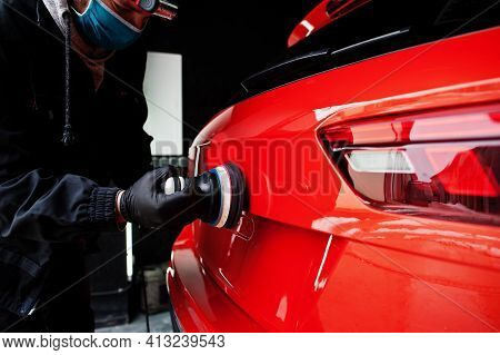 Car Detailing Concept. Man In Face Mask With Orbital Polisher In Repair Shop Polishing Orange Suv Ca