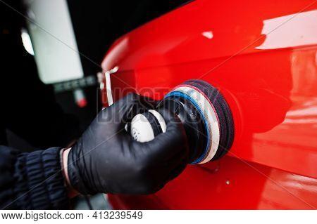 Car Detailing Concept. Hands Of Man With Orbital Polisher In Repair Shop Polishing Orange Suv Car.