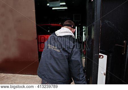 Car Detailing Concept. Man  In Repair Shop Polishing Orange Suv Car.