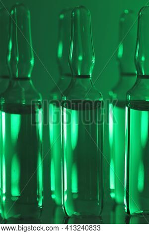 Biotechnology And Science. Medicine And Pharmacology Concept.glass Ampoules Set In Green Light.organ