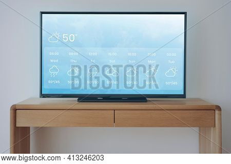 Smart TV with weather forecast on wooden stand