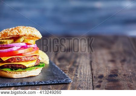 Vegetarian Cheeseburger Made With Two Meat Substitute Patties, Slices Of Melted Cheese, Onions, Pick