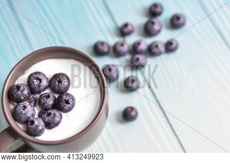 Cup With Yogurt And Blueberries On Background Of Blue Boards. Delicious Milk Yogurt And Scattered Be
