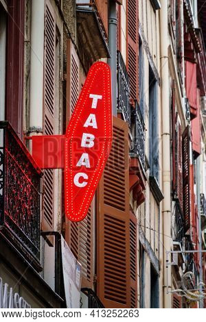 BAYONNE, FRANCE - CIRCA DECEMBER 2020: French red tobacconist sign outside tobacco shop.