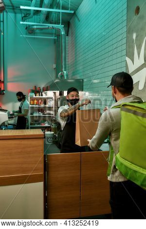Chef With A Mask On His Face Is Giving A Bag Of Food To A Food Delivery Man. Delivery Young Man Is T