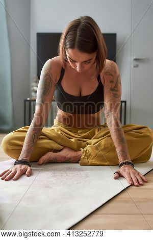 Young Caucasian Woman Practicing Yoga Uddiyana Bandha Abdominal Lock Exercise While Sitting On Floor