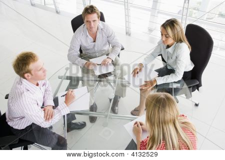 Four Businesspeople In Boardroom With Paperwork