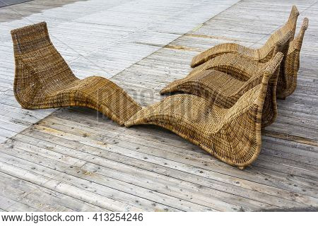 Wicker Rattan Deck Chairs On A Wooden Deck In A Summer Park