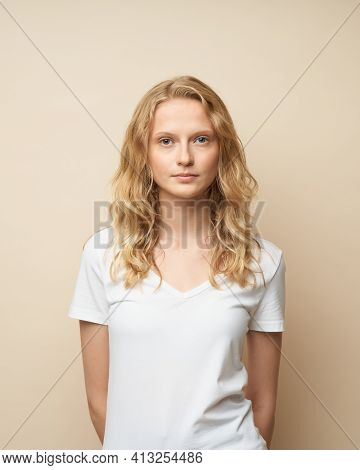Waist Up Portrait Of Beautiful Young Serious Clever Blonde Woman Without Makeup On Beige Wall. Prett