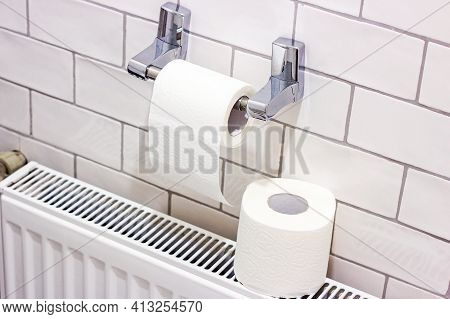 White Toilet Paper Roll On The Holder In The Lavatory.
