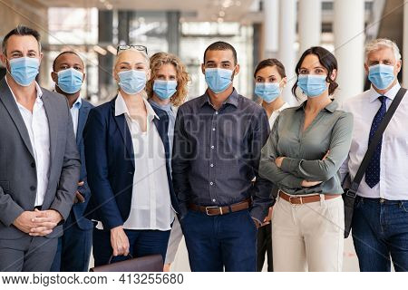 Portrait of successful group of business team wearing surgical mask for safety against coronavirus. satisfied businessmen and businesswomen standing together with face masks and looking at camera.