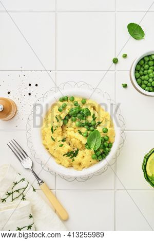 Mashed Potato With Butter, Green Peas, Onions, Basil On White Ceramic Tile Background. Top View With