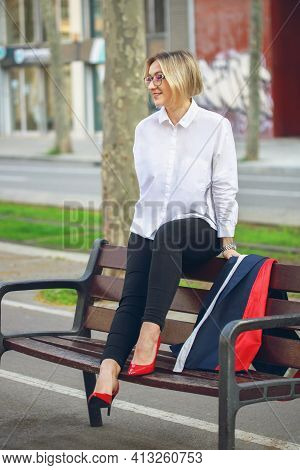 Young Funny Business Woman Sitting On A Bench After Work. Beautiful Blond Woman With White Shirt And