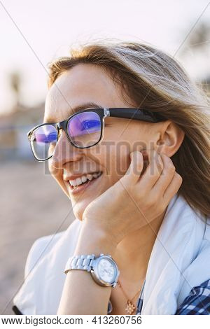 Young Blond Woman At The Beach On A Cold Day. Portrait Of Cheerful Woman With Glasses. Vertical Phot