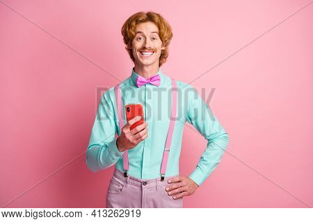 Photo Of Young Funky Positive Funky Funny Man Wear Suspender Bow Tie Using Smartphone Isolated On Pi