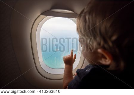 Resumption Of Flights, Opening Of Borders Concept. A Small Child Looks At The Ocean From The Window