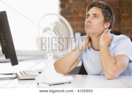 Businessman In Office With Computer And Fan Cooling Off