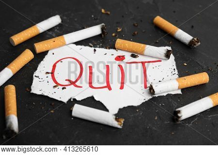 Cigarette Stubs And Paper With Word Quit On Black Slate Table. Giving Up Smoking Concept