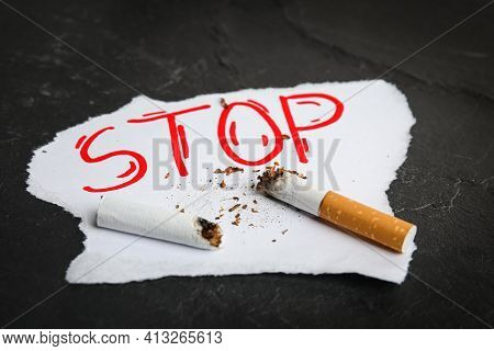 Cigarette Stubs And Paper With Word Stop On Black Table. Quitting Smoking Concept