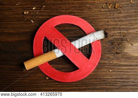 Cigarette With Prohibition Sign On Wooden Table, Top View. Quitting Smoking Concept