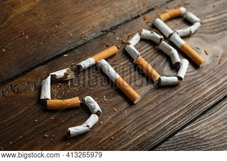 Word Stop Of Cut Cigarettes On Wooden Table. Quitting Smoking Concept