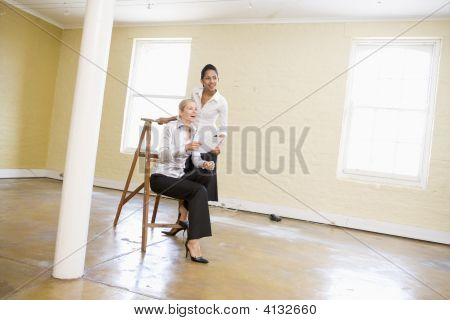 Two Women In Empty Space With Ladder Holding Paper And Smiling