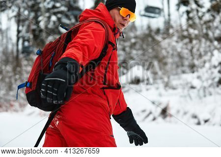Male Snowboarder In A Red Suit Rides On The Snowy Hill With Snowboard, Skiing And Snowboarding Conce
