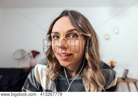 Funny Millennial Female Vlogger Wearing Glasses And Headphones Looking At Camera. Freelancer Holding