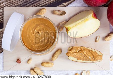 Top View Of Fresh Homemade Crunchy Peanut Butter With Nuts And Apples On Light Wooden Background In
