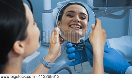 Woman With Perfect Teeth Looking In Mirror Near Stomatologist In Dental Clinic, Blurred Foreground.