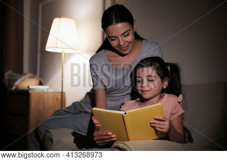Little Girl With Mother Reading Fairy Tale At Home In Evening
