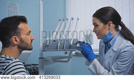 Stomatologist Pointing At Teeth Model Near Patient In Dental Clinic.