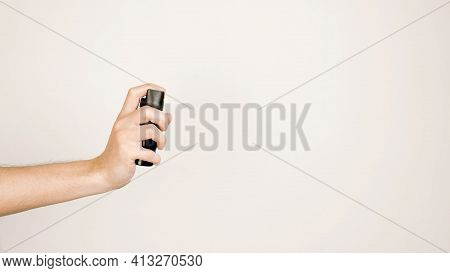 Male Hand Holding Pepper Spray On A Light Background, Copy Space. Self-defense Concept.