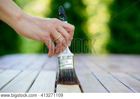 Hand Holding A Paintbrush Applying Varnish Paint On A Wooden Garden Table - Painting And Caring For